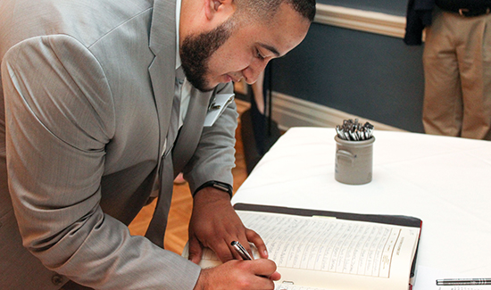 Nicholas Ramos signs the Supreme Court Roll book