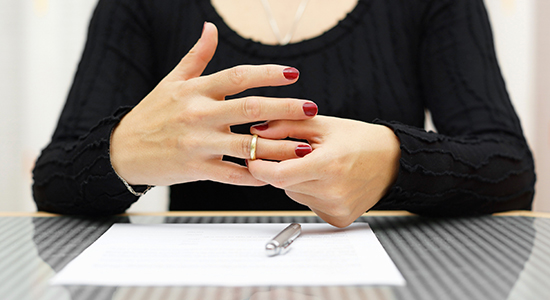 woman signs divorce papers and removes ring