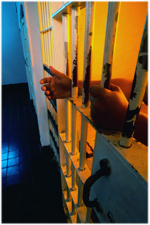 Photo: Hands behind prison 