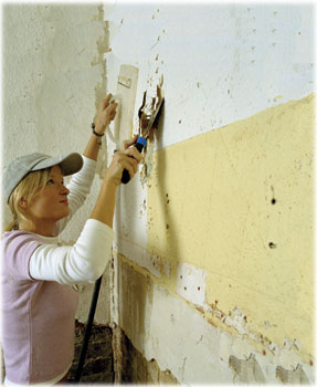 worker scraping walls