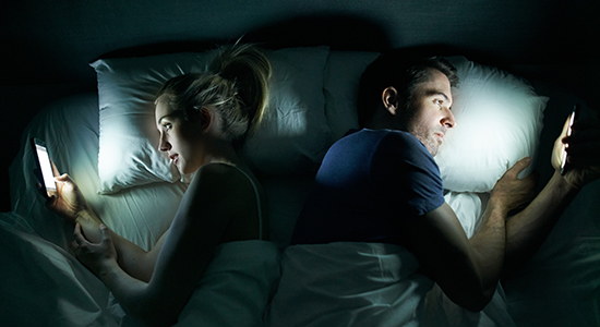couple in bed looking at phones