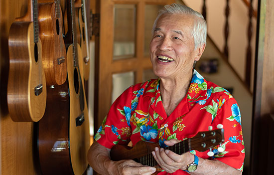 elderly man laughs playing guitar