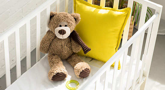 teddy bear in crib